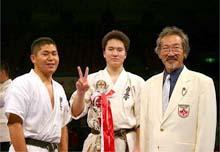 念願の初タイトルに思わずVサインの寺浦(右:岡田師範、左:重量級4位・當)